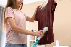 Jeune femme cuisant ses vêtements à la vapeur à la maison photos stock