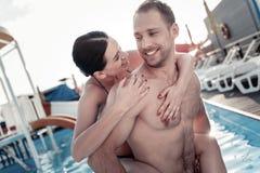Jeune femme curieuse interrogeant l'ami au sujet de quelque chose dans la piscine Photographie stock