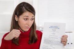 Jeune femme déçue regardant fixement le contrat d'affaires en allemand Image stock