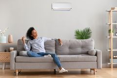 Jeune femme décontractée africaine s'asseyant sur le divan respirant l'air frais image stock