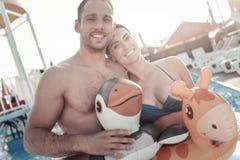 Jeune femme décontractée et homme rayonnant tout en nageant dans la piscine Photo stock