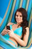 Jeune femme décontractée regardant le téléphone portable dedans Photos stock