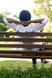 Jeune femme décontractée s'asseyant sur un banc de parc Photo stock
