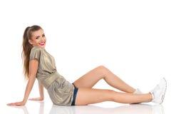 Jeune femme décontractée s'asseyant sur un plancher Images libres de droits