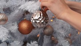 Jeune femme décorant l'arbre de Noël avec des babioles La préparation de nouvelle année, se ferment  banque de vidéos