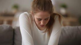 Jeune femme dépendante soucieuse seul s'asseyant sur le divan à la maison banque de vidéos
