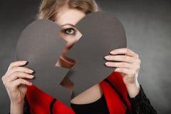 Jeune femme déprimée couverte par le coeur brisé photo stock