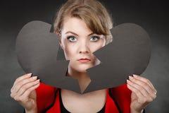 Jeune femme déprimée couverte par le coeur brisé Image libre de droits