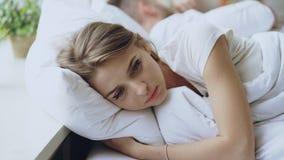 Jeune femme déprimée se situant dans le lit et le renversement feeeling après querelle avec son boylfriend dans le lit à la maiso Photos libres de droits