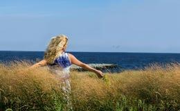 Jeune femme détendant à l'océan Images stock