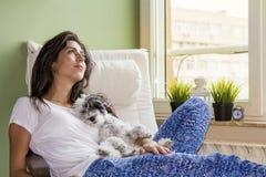 Jeune femme détendant à la maison étreignant son petit chien Photo libre de droits