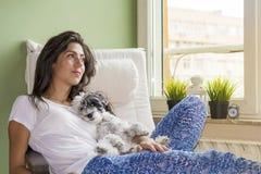 Jeune femme détendant à la maison étreignant son petit chien Photographie stock libre de droits
