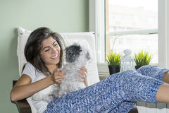 Jeune femme détendant à la maison étreignant son petit chien Photos stock