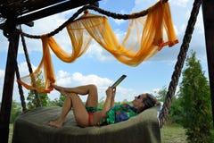 Jeune femme détendant dans l'hamac avec le comprimé Photo libre de droits