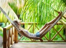 Jeune femme détendant dans l'hamac dans une station de vacances tropicale Photos libres de droits