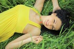 Jeune femme détendant dans l'herbe Photographie stock