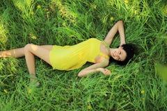 Jeune femme détendant dans l'herbe Photo stock