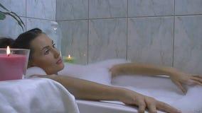 Jeune femme détendant dans la baignoire banque de vidéos