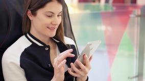 Jeune femme détendant dans le fauteuil en cuir confortable dans le centre commercial utilisant le téléphone portable passant en r banque de vidéos