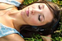 Jeune femme détendant dans le pré images stock