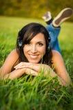 Jeune femme détendant dans le pré image stock