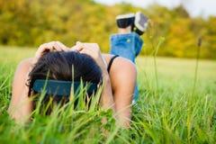 Jeune femme détendant dans le pré photos stock