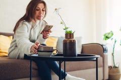 Jeune femme détendant dans le salon utilisant le smartphone et le café potable D?cor int?rieur photo stock