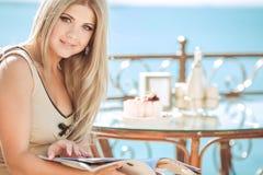 Jeune femme détendant dans un café extérieur Photos libres de droits