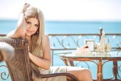 Jeune femme détendant dans un café extérieur Photos stock