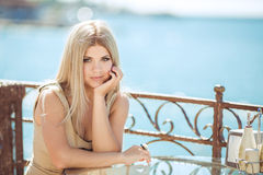 Jeune femme détendant dans un café extérieur Photographie stock libre de droits