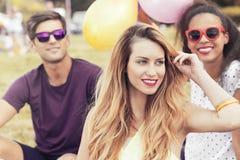 Jeune femme détendant dehors avec des amis Photographie stock libre de droits