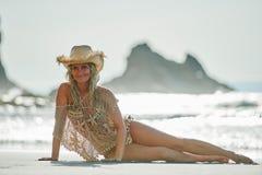 Jeune femme détendant sur la plage dans le jour d'été Photographie stock libre de droits