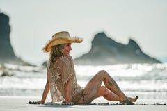 Jeune femme détendant sur la plage dans le jour d'été Images libres de droits