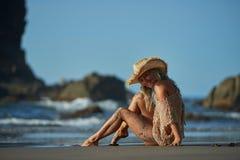 Jeune femme détendant sur la plage dans le jour d'été Photos libres de droits