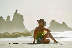 Jeune femme détendant sur la plage dans le jour d'été Photo stock