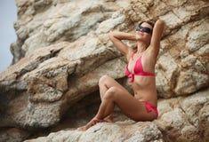 Jeune femme détendant sur la roche à la plage Images stock