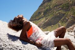 Jeune femme détendant sur la roche dehors Image stock