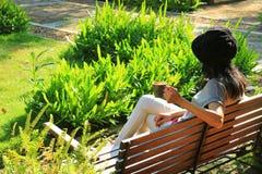 Jeune femme détendant sur le banc en bois dans le jardin vert vibrant tenant une tasse de café chaud photographie stock