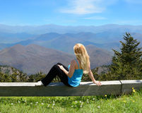 Jeune femme détendant sur le dessus de la montagne Photo stock