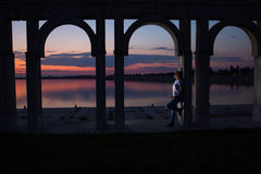 Jeune femme détendant sur le lac au coucher du soleil Images stock