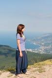Jeune femme détendant sur une roche et appréciant la beauté du paysage marin se tenant sur le dessus de montagne Voyage, sain Photo stock