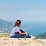 Jeune femme détendant sur une roche et appréciant la beauté du paysage marin sitiing sur le dessus de montagne Voyage, sain Image libre de droits