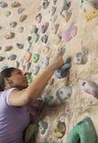 Jeune femme déterminée escaladant un mur s'élevant dans un gymnase s'élevant d'intérieur Image libre de droits
