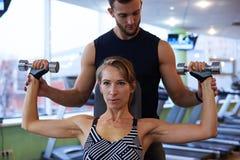 Jeune femme déterminée fléchissant le biceps avec l'entraîneur personnel dans g image libre de droits