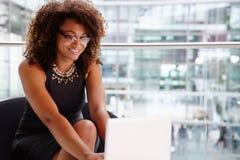 Jeune femme d'affaires à l'aide de l'ordinateur portable dans l'intérieur moderne Photo stock