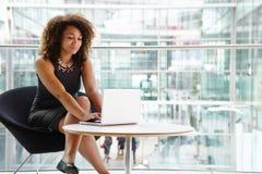 Jeune femme d'affaires à l'aide de l'ordinateur portable dans l'intérieur moderne Image libre de droits