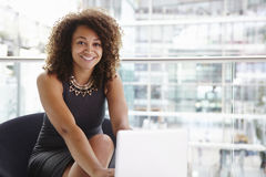 Jeune femme d'affaires à l'aide de l'ordinateur portable, regardant à l'appareil-photo Photographie stock libre de droits