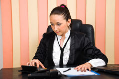 Jeune femme d'affaires à l'aide de la calculatrice Image stock