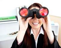 Jeune femme d'affaires à l'aide des jumelles dans son bureau Photos stock
