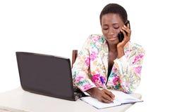 Jeune femme d'affaires à l'aide d'un téléphone portable et d'un ordinateur portable photographie stock